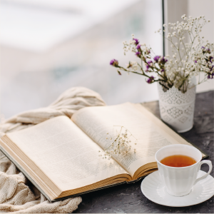 Open book, flowers and cup of tea on a desk